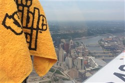 Navy pilot and Steelers superfan Sean Hovanec flies his plane above Downtown with his trusty Terrible Towel by his side.