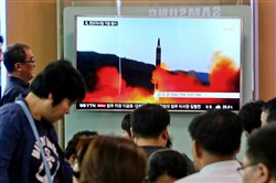 People watch a TV news program on Sunday showing a file image of a missile launch by North Korea at the Seoul Railway Station in Seoul, South Korea. North Korea fired a midrange ballistic missile Sunday, U.S. and South Korean officials said, in the latest weapons test for a country speeding up its development of nuclear weapons and missiles.