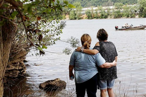 Kathie Brandy, left, and her sister-in-law stand on the banks of the Ohio River on Monday, as crews search for Ms. Brandy's daughter Helene, who has been missing since Saturday after her and friend went over a dam while kayaking.