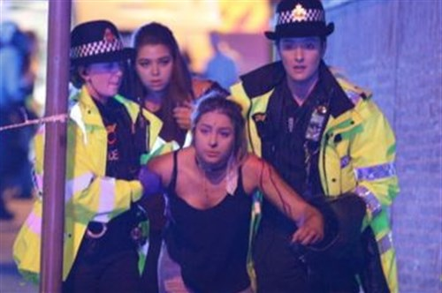 An Ariana Grande fan is escorted away from the Manchester Arena after an explosion in England Monday night.
