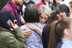 Retail staff hug each other after being evacuated from the Arndale Centre shopping mall Tuesday in Manchester, England, following a security alert the day after a terror attack.