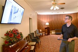 Funeral director Scott Beinhauer Friday sets up a television screen in a viewing room created for watching cremations in Beechview. With the rise in cremations, Beinhauer Funeral Home, which has been doing cremations since the 1920's, renovated a viewing room to give family members the opportunity to be more involved in the cremation process.