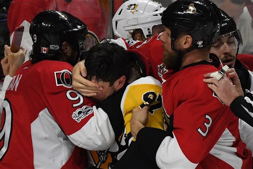 Sidney Crosby, center, is roughed up against the Senators Tuesday at the Canadian Tire Center in Ottawa, Ontario.
