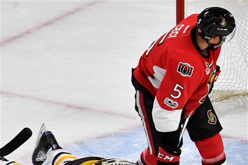 Penguins forward Jake Guentzel goes down after taking a check from Senators defenseman Mark Stone as Cody Ceci stands over him in the first period of Game 6 Tuesday at Canadian Tire Centre in Ottawa.