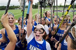 "Hampton's Rachel Hirst, with ink on her arm reading ""No Regrets,"" brings her team together after beating Oakland Catholic in the WPIAL Class 2A girls lacrosse championship Thursday."