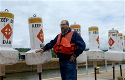 John Dilla, chief of the Army Corps' locks and dams branch, stands with several water buoys in this file photo.