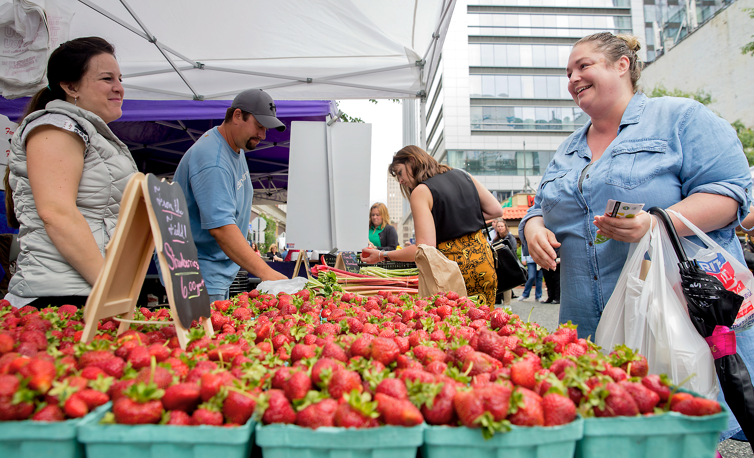 20170525acMarketSquare07-6 Carrie Stewart, left, of Bloomfield, buys two boxes of strawberries from Amy Andrews at the Market Square Farmers Market on Thursday, May 25, 2017. Andrews husband, Chad Andrews, of St. Thomas Township, is the third generation fruit grower of Andrews Farm Market.