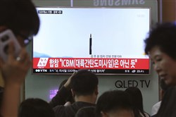 People watch a TV news program showing a file image of a missile launch conducted by North Korea on May 21 at the Seoul Railway Station in Seoul, South Korea. With North Korea's nuclear missile threat in mind, the Pentagon is planning a missile defense test next week that for the first time will target an intercontinental-range missile.