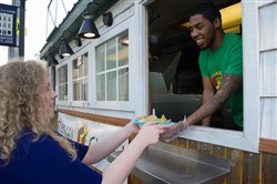 Kristina Clark picks up her bowl of chili from Trevon Kendrick at the Revival Chili food truck.