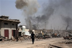 In this Tuesday, May 9, 2017 file photo, smoke rises during heavy fighting between Islamic State militants and Iraqi special forces in the industrial area of west Mosul, Iraq. In Mosul, Iraqi forces are steadily closing in on remaining pockets of territory held by IS, but unlike past urban battles against them in Iraq, the militants still hunkered down in the city are mounting a stiff resistance, and the more the battle stretches out, the greater the risk for civilians remaining behind.