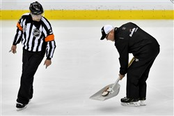 A member of the ice crew removes a catfish that was thrown onto the ice Monday at PPG Paints Arena in Game 1 of the Stanley Cup final between the Penguins and the Nasvhille Predators.