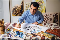 Majid Roohafza works on Persian calligraphy in the studio of his Sewickley home.