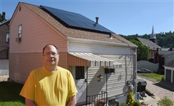 Randy Bondi stands in front of his Etna home, where he had 12 solar panels mounted on the roof as part of a program funded through the Heinz Endowments. The panels provide nearly all of the electricity he consumes during the year.