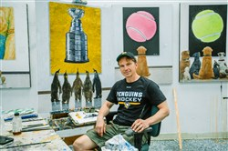 "Artist Tom Mosser sits in his studio next to his unfinished painting, ""Penguins at the Museum,"" at his studio in Etna."