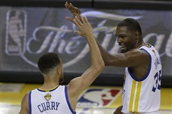 Golden State Warriors guard Stephen Curry and forward Kevin Durant react after scoring Thursday against the Cleveland Cavaliers during the first half of Game 1 of the NBA Finals in Oakland, Calif.