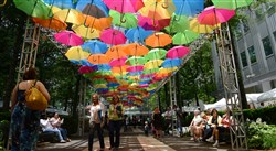 People walk under the Umbrella Sky Project during the opening day of the Three Rivers Arts Festival Friday, June 2, 2017, in Downtown Pittsburgh.