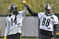 Sammie Coates and Darrius Heyward-Bey fist bump during practice in October on the South Side.