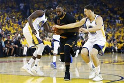 LeBron James of the Cleveland Cavaliers is defended by Draymond Green and Klay Thompson of the Golden State Warriors during the first half in Game 2 of the 2017 NBA Finals.
