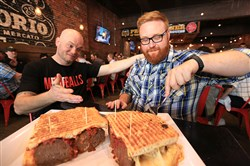 "Donnie Amman, left, chef de cuisine at Emporio, watches ""Ginormous Food"" host Josh Denny cut  into The Six Pack, a ciabatta sandwich packed with six huge meatballs."
