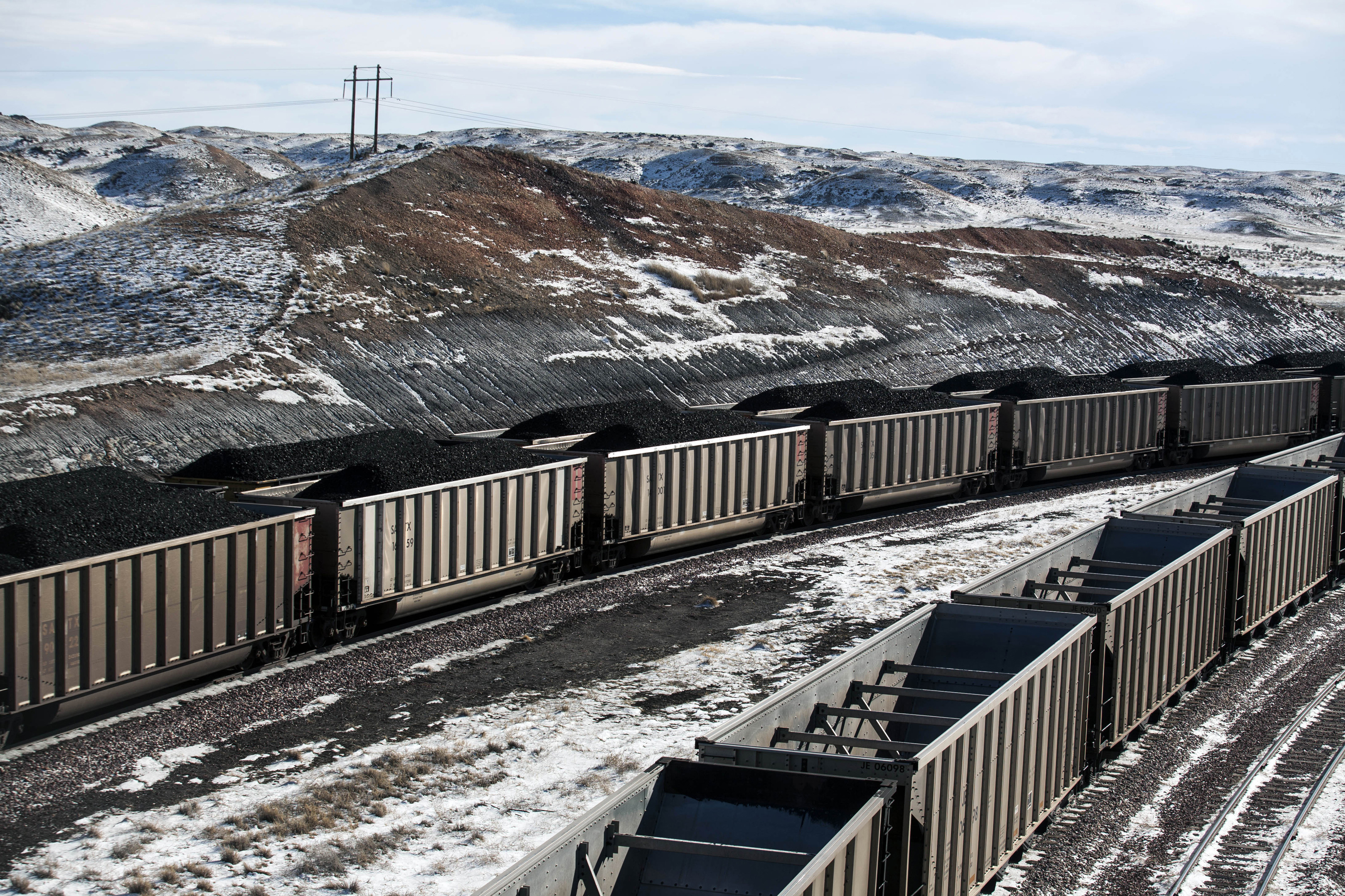AP Explains Trump Coal-2 FILE - In this Jan. 9, 2014, file photo, rail cars are filled with coal and sprayed with a topper agent to suppress dust at Cloud Peak Energy's Antelope Mine north of Douglas, Wyo. President Donald Trump says withdrawing from a global climate change agreement will boost the U.S. economy but existing market forces have had far more of an effect on the fossil fuel industries than climate regulations. For at least three years now, the coal industry has been reeling from growing competition from natural gas, wind and solar power. (Ryan Dorgan/The Casper Star-Tribune via AP, File)