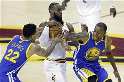 Cavaliers forward LeBron James drives between Warriors Matt Barnes, left, and Andre Iguodala Wednesday during the Game 3 of the NBA Finals in Cleveland.