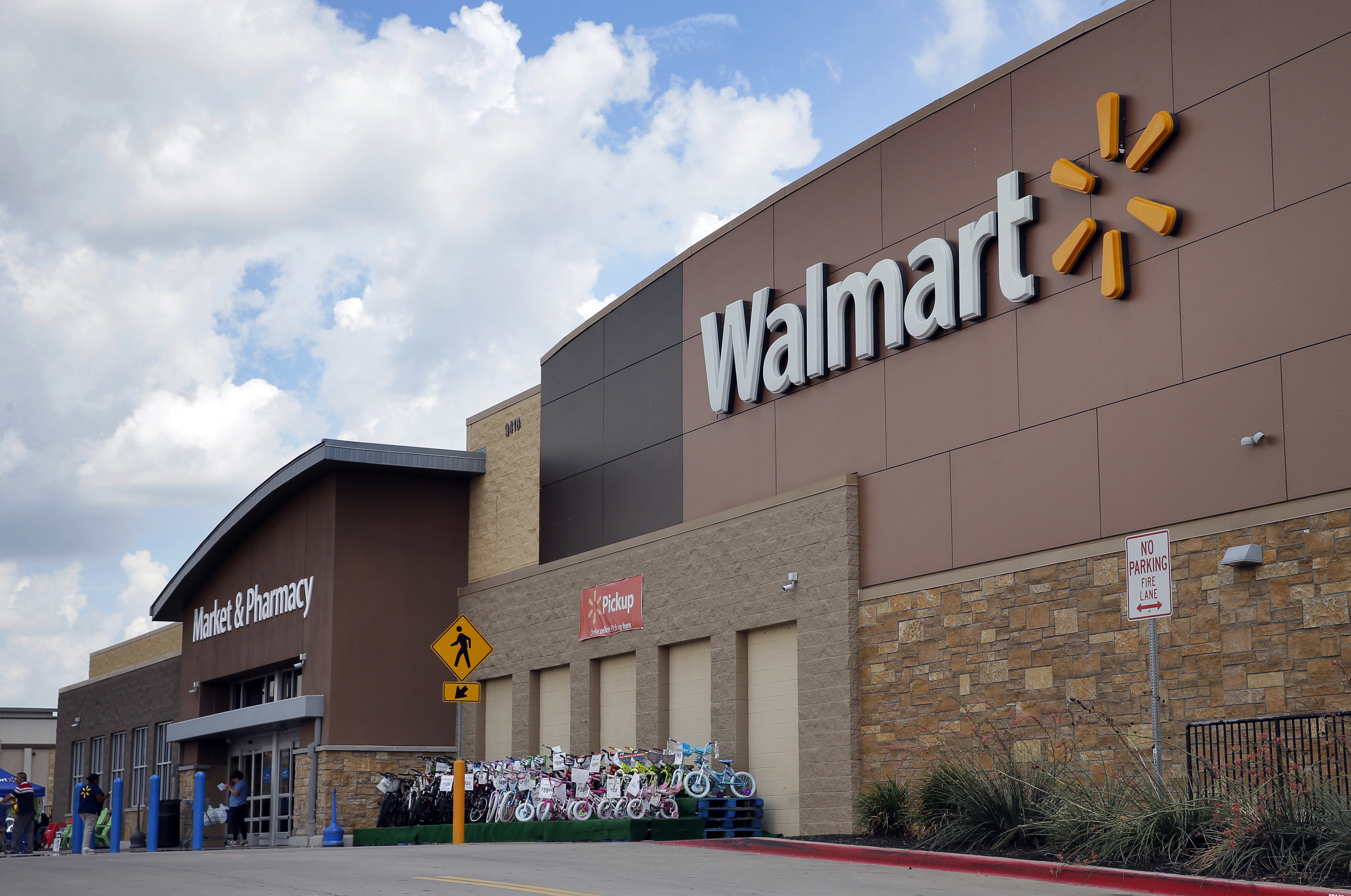 Climate Companies Q A FILE - In an Aug. 26, 2016 file photo, people walk in and out of a Walmart store, in Dallas. President Donald Trump's decision to abandon the Paris climate agreement will have different impacts on different US companies, depending on what they make and whether they do business overseas. Walmart, which launched program in April 2017 to remove one gigaton of emissions from its supply chain by 2030, said after Trump's announcement that its own commitment to renewable energy and lower emissions was good for business and the environment. (AP Photo/Tony Gutierrez, File)