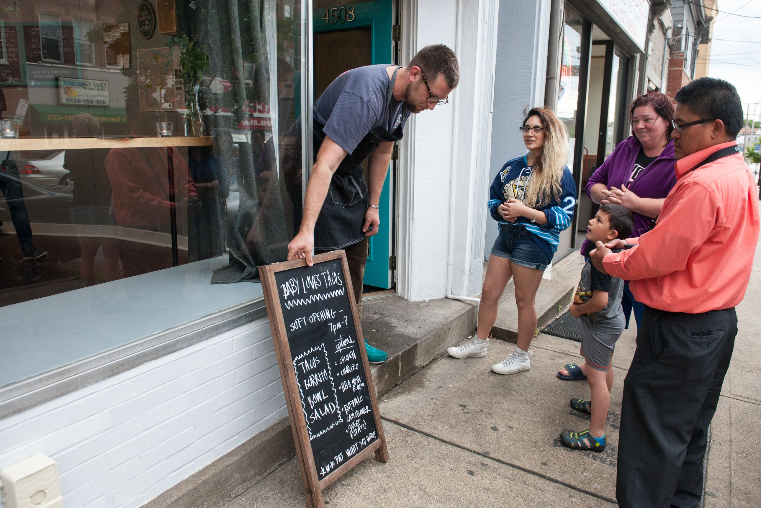 20170608smsTacos06-5 Zack Shell of Point Breeze puts out his blackboard menu as people wait for him to be ready for the soft opening at his new restaurant, Baby Loves Tacos in Bloomfield.
