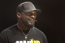 "Head coach of the Steelers, Mike Tomlin, speaks at ManUp Pittsburgh on Saturday at Victory Family Church in Cranberry. ""What I do is not what I am,"" he said. Tomlin said that he aspires to be a ""godly father."""