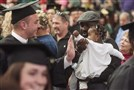 Donte Ebo holds out the hand of his 1-year-old daughter Taylor to give high-fives to passing graduates at the commencement ceremony May 13 at Slippery Rock University.