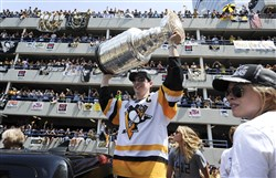 Sidney Crosby raises the Stanley Cup on the Boulevard of the Allies in Pittsburgh on June 14, 2017, during the Pittsburgh Penguins' victory parade and rally.
