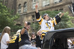 Penguin Carl Hagelin gives the No. 1 sign on Wednesday at the Penguins' Stanley Cup victory parade and rally in Downtown Pittsburgh. Hagelin played through the playoffs while recovering from a broken fibula.