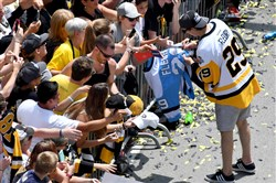 Penguins goalie Marc-Andre Fleury signs autographs for fans along the Boulevard of the Allies during the team's parade Wednesday, June 14, 2017, in Pittsburgh.