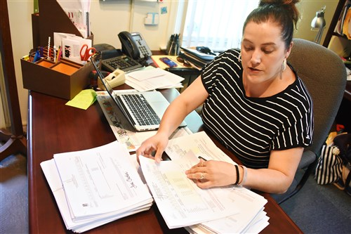 Alexis Trubiani, Clairton City school district's student services liaison and public relations director, reviews stacks of invoices to track charter and cyber schools enrollment and payments by the Clairton City School District in her office. Ms. Trubiani said that in her first year, the school district was billed for $70,000 for students that were not from Clairton.