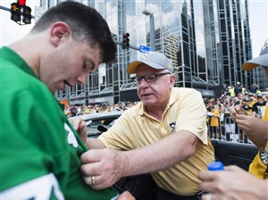 Penguins general manager Jim Rutherford signs a fan's jersey at the team's victory parade June 14, 2017 at Grant Street and Boulevard of the Allies.