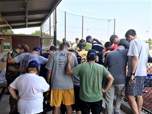 U.S. Rep. Mike Doyle, center in a Roberto Clemente jersey, leads members of the Congressional Democrats baseball team in prayer after the team learned of the shooting June 14 at the field where their Republican opponents practice.