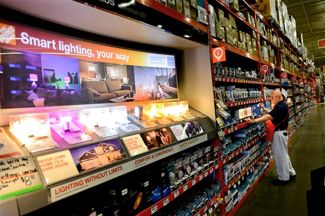 Jay Chiusano, a pro associate at Home Depot in East Liberty, arranges the shelves in the lighting department.