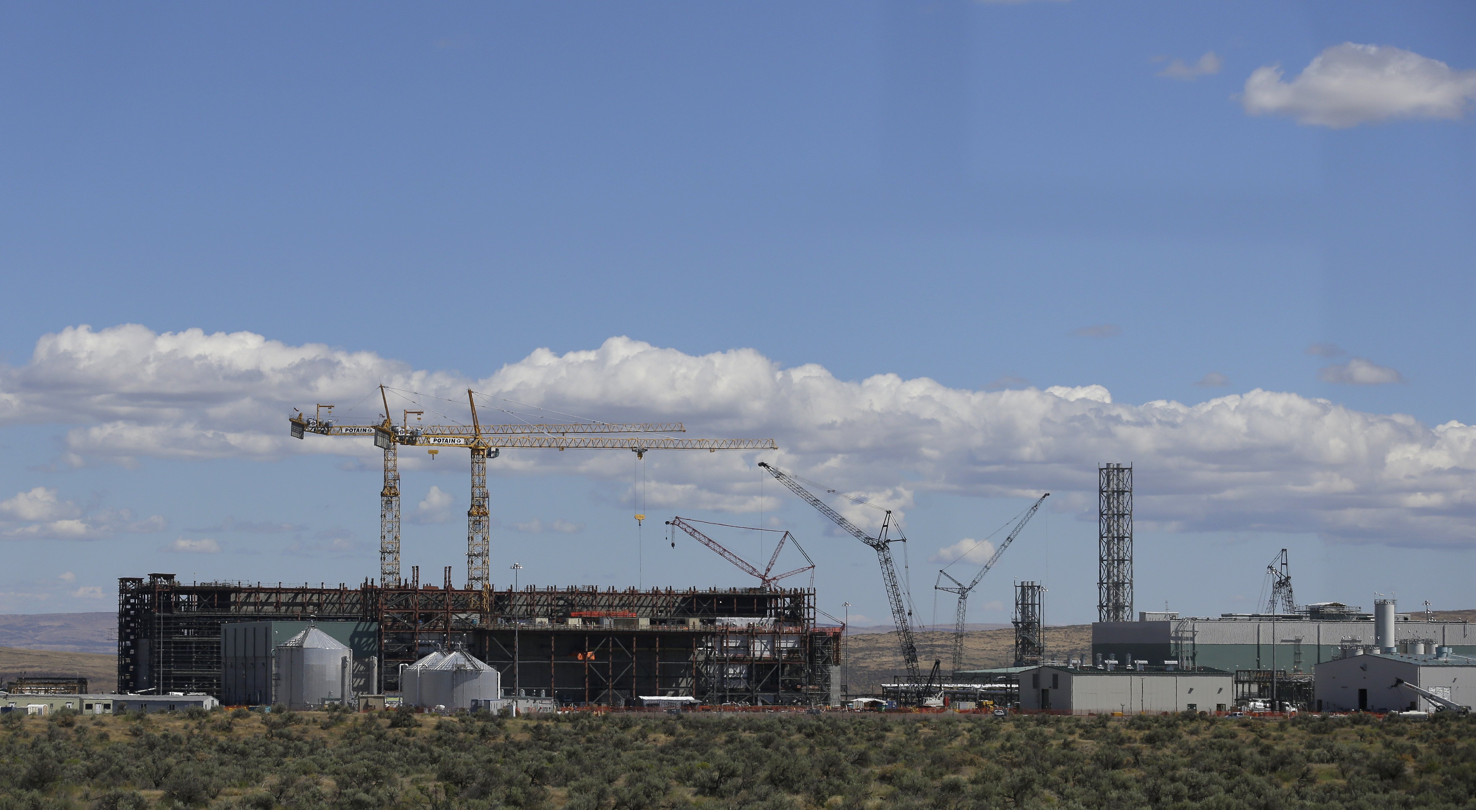 Hanford Nuclear Waste-1 In this photo taken July 11, 2016, cranes tower above a waste treatment plant under construction on the Hanford Nuclear Reservation near Richland, Wash. The U.S. Energy Department's top official at Washington state's severely contaminated nuclear reservation says future accidental nuclear radiation releases are likely because of aging site infrastructure and inadequate cleanup funding. Hundreds were evacuated May 9, 2017 when the roof of a 1950s rail tunnel storing a lethal mix of waste from plutonium production collapsed. Tests show no radiation was released. (AP Photo/Ted S. Warren)