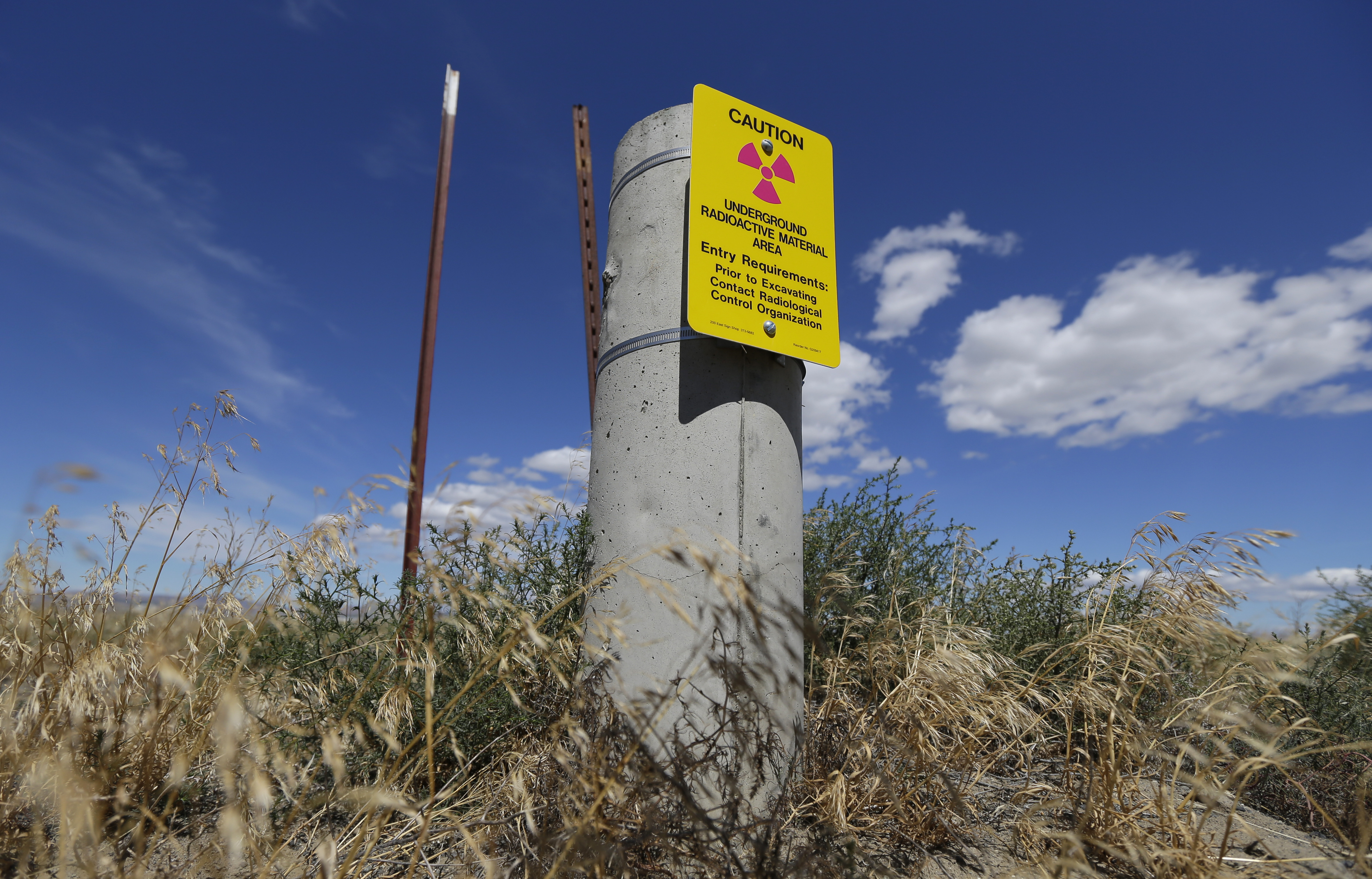 Hanford Nuclear Waste-6 In this photo taken July 11, 2016, a sign warns of radioactive material stored underground on the Hanford Nuclear Reservation near Richland, Wash. The U.S. Energy Department's top official at Washington state's severely contaminated nuclear reservation says future accidental nuclear radiation releases are likely because of aging site infrastructure and inadequate cleanup funding. Hundreds were evacuated May 9, 2017 when the roof of a 1950s rail tunnel storing a lethal mix of waste from plutonium production collapsed. Tests show no radiation was released. (AP Photo/Ted S. Warren)