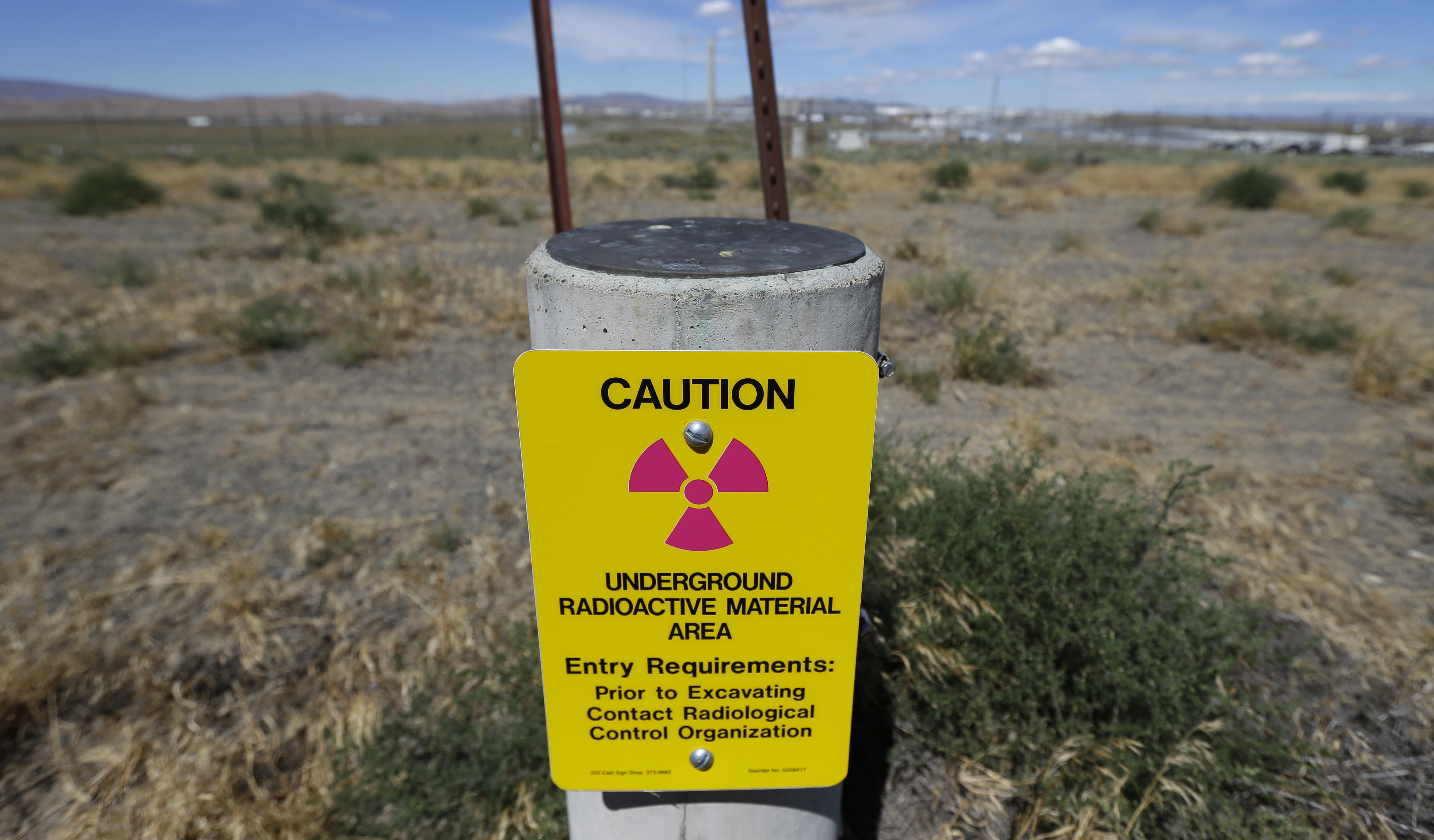 Hanford Nuclear Waste In this photo taken July 11, 2016, a sign warns of radioactive material stored underground on the Hanford Nuclear Reservation near Richland, Wash. The U.S. Energy Department's top official at Washington state's severely contaminated nuclear reservation says future accidental nuclear radiation releases are likely because of aging site infrastructure and inadequate cleanup funding. Hundreds were evacuated May 9, 2017 when the roof of a 1950s rail tunnel storing a lethal mix of waste from plutonium production collapsed. Tests show no radiation was released. (AP Photo/Ted S. Warren)