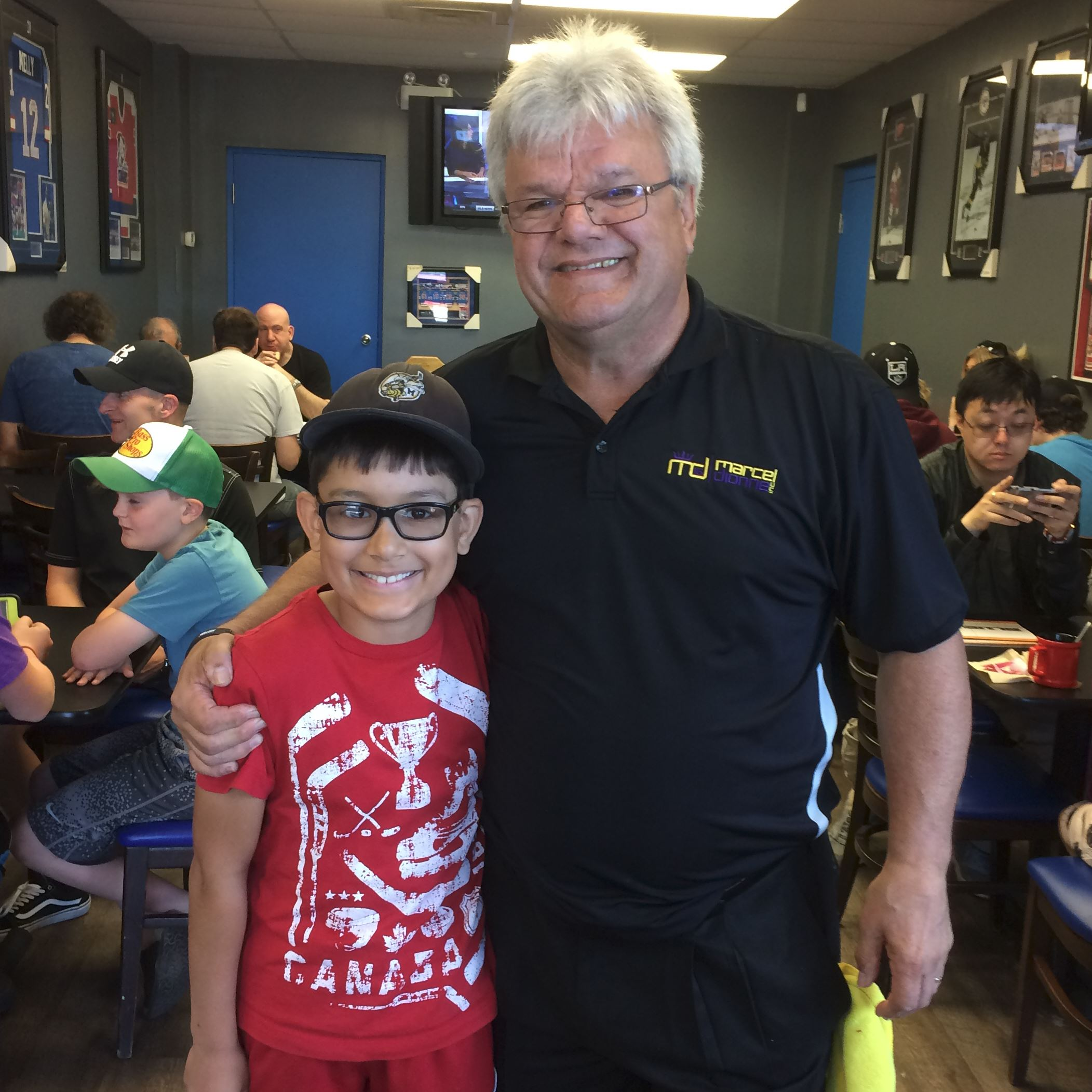 Marcel Dionne Hockey great Marcel Dionne poses for a photograph with hockey player Jesse Batz at Mr. Dionne's daughter's Blue Line Diner in Niagara Falls, Ont.