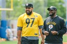Steelers coach Mike Tomlin watches practice with Cam Heyward on Thursday.