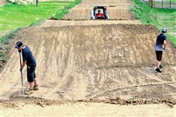 Matt Sedlak, left, and Brandon Hawkins work to smooth the surface of the South Park BMX race track this past Saturday.