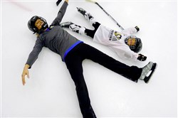 Counselor Jessica Duncan makes a snow angel with 6-year-old Danika Johns of Apollo during a blind hockey camp run by Envision Blind Sports and Pittsburgh Penguins Blind Hockey at the UPMC Lemieux Sports Complex in Cranberry in June.