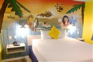The interior of a bungalow room at Legoland Beach Retreat features wallpaper images of Lego Minifigs.