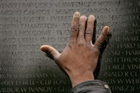 A man places his hand on the Vietnam Veterans Memorial in Washington, D.C., where the names of 58,000 Americans killed in the Vietnam War are listed.