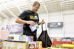 "Ben Roethlisberger packs bags of food that will be delivered to the Greater Pittsburgh Community Food Bank as part of an addition to the camp that is partnered with The Kraft Heinz Company Foundation and the ""Fight Hunger with a Pro"" program. Kids participated in drills and activities during the 9th Annual Football ProCamp on Sunday at the UPMC Rooney Sports Performance Complex."