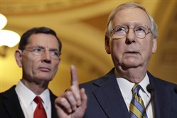 In this May 23, 2017, file photo, Senate Majority Leader Mitch McConnell of Ky., right, accompanied by Sen. John Barrasso, R-Wyo., speaks on Capitol Hill in Washington.