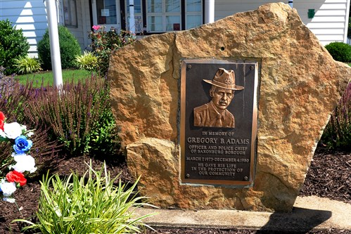 A stone memorial to former Saxonburg Police Chief Gregory Adams, who was killed Dec. 4, 1980, stands in front of the Saxonburg municipal building. The FBI has issued a renewed plea for assistance in finding the fugitive wanted in the homicide.