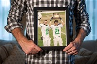 Zach Challingsworth holds a photo of him and his older brother Tyler, right, from their days playing football together for South Fayette High School.