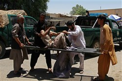 Afghan men carry a victim of a powerful car bomb in Lashkar Gah, the capital of Helmand province, on June 22. More than 20 people were killed when a powerful car bomb struck a bank in Afghanistan's Lashkar Gah city as government employees were queueing to withdraw salaries, the latest bloody attack during the holy month of Ramadan.